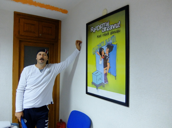 """Samir in his office, Slogan on the poster: """"Shake the state! When the young vote."""", Frank Schulz"""